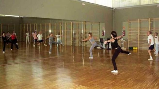 Varias personas practicando ejercicio en un gimnasio.