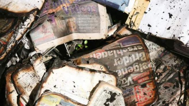 Restos calcinados de ejemplares del periódico en la sede atacada la madrugada de este domingo.