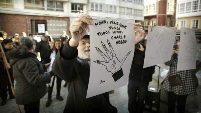 """El dibujante gallego 'Siro' porta una ilustración en la que se podía leer en gallego """"Hoy más que nunca todos somos 'Charlie Hebdo'"""", durante la concentración convocada en la plaza del Humor de A Coruña."""