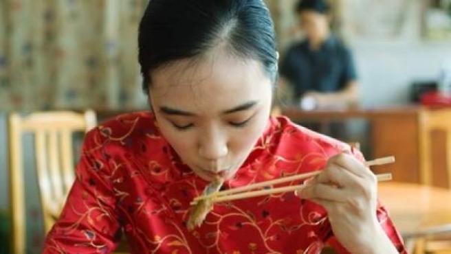 Una mujer asiática come tallarines en un restaurante.