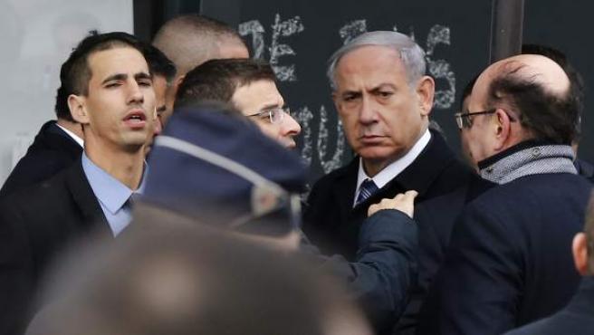 El primer ministro israelí, Benjamin Netanyahu (2-d), llega rodeado por personal de seguridad durante su visita al supermercado Kosher en el que cuatro judíos perdieron la vida en un atentado yihadista, en París (Francia). Netanyahu llegó el domingo a la capital para participar en la multitudinaria marcha en honor de las 17 personas que perdieron la vida en los atentados de la semana pasada en París.