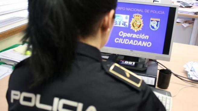 Una agente de policía consulta un ordenador.