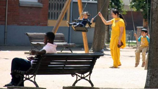 Una mujer hindú columpia a unos niños en un parque de Vic (Barcelona), donde un chico de origen subsahariano escucha música en un banco.