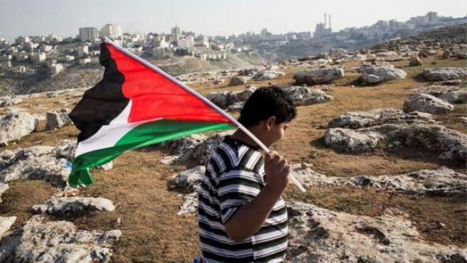 Un niño, con una bandera Palestina.