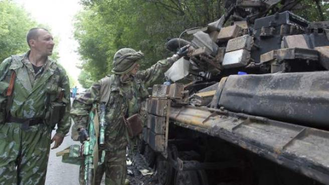 Unos activistas prorrusos observan los restos carbonizados de un tanque ucraniano a las afueras de Donetsk, Ucrania.