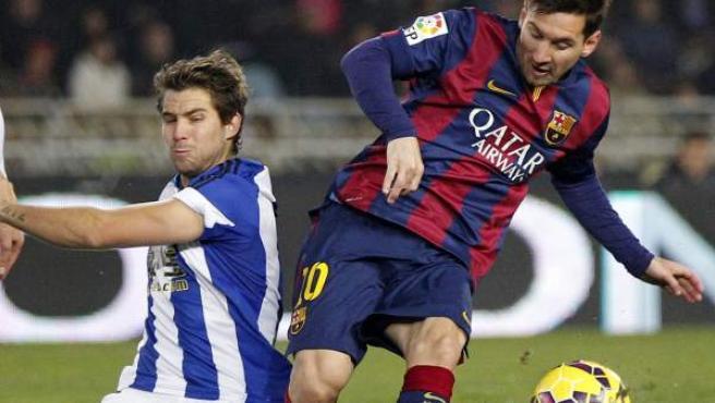 El futbolista del Barça Leo Messi (dcha.), presionado por un jugador de la Real.