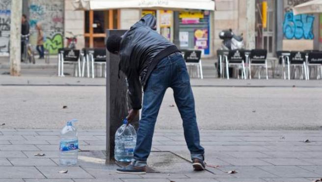 Un barcelonés, llenando diversas garrafas de agua en una fuente pública de Barcelona.