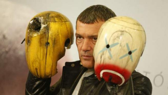 Antonio Banderas posa con las cabezas de dos de los robots que aparecen en la película 'Autómata'.