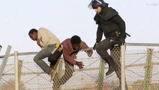 Un agente de Policía junto a inmigrantes en la valla de Melilla, fronteriza con Marruecos.