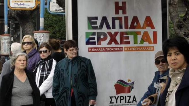 Varias personas esperan el autobús junto a un cartel del partido griego izquierdista Syriza.