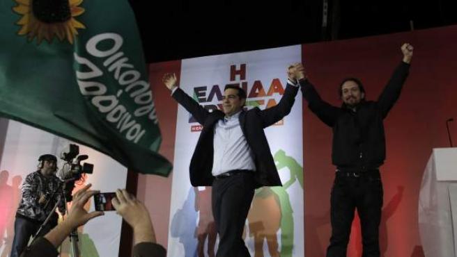 El líder del partido español Podemos, Pablo Iglesias (d), saluda acompañado por el líder del partido izquierdista griego Syriza, Alexis Tsipras (2d), en Atenas (Grecia)