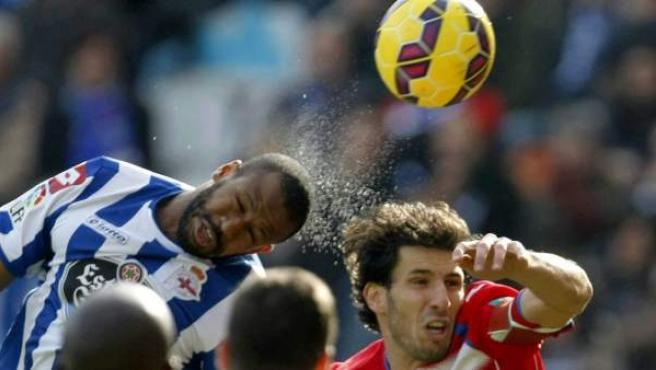 El defensa brasileño del Deportivo de La Coruña, Sidnei Da Silva (i), salta a por la pelota junto al defensa del Granada, Diego Mainz (d).