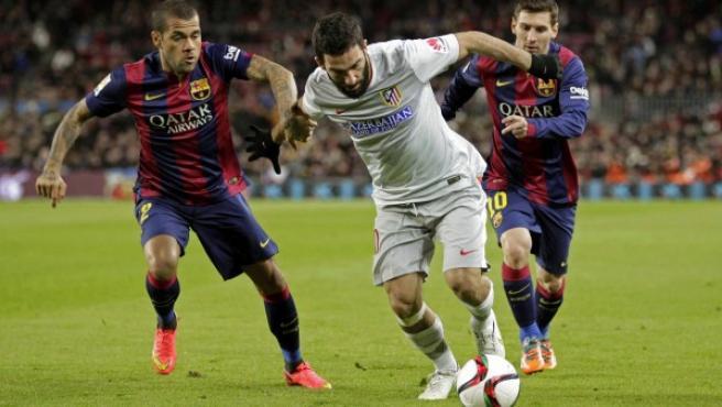 El centrocampista turco del Atlético de Madrid Arda Turán (c) controla el balón ante los jugadores del FC Barcelona, el brasileño Dani Alves (i), y el argentino Lionel Andrés Messi (d) , durante el partido de ida de los cuartos de final de la Copa del Rey.