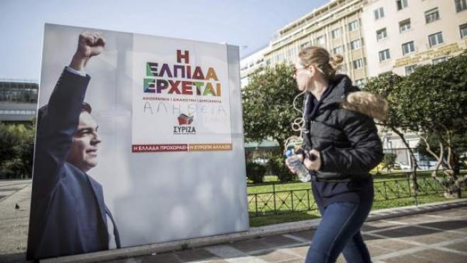 Una joven observa un cartel electoral del líder de Syriza, Alexis Tsipras, en el centro de Atenas (Grecia).