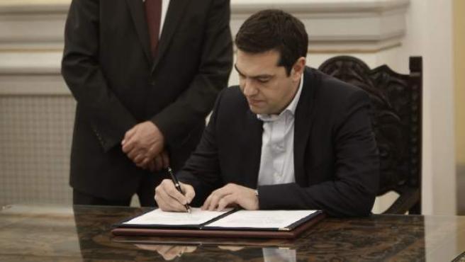 El líder de la izquierdista Syriza, Alexis Tsipras (d), firma un documento tras jurar como nuevo primer ministro griego