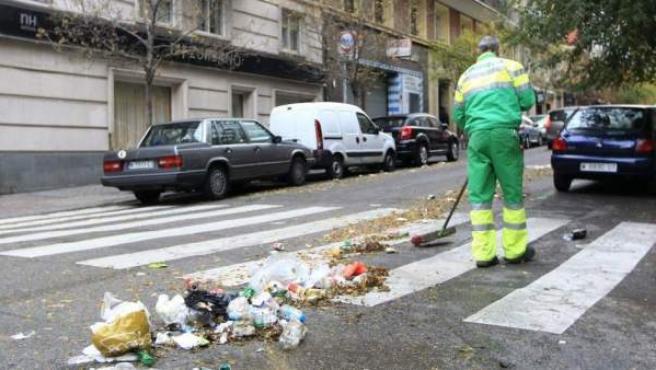 Personal del servicio de limpiezas de Madrid limpia los residuos urbanos acumulados en una calle.