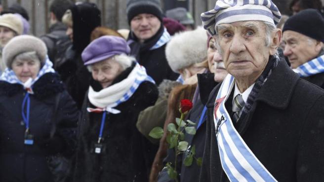 Exprisioneros se concentran ante el campo de concentración nazi de Auschwitz I antes de depositar flores ante el llamado Muro de la Muerte.