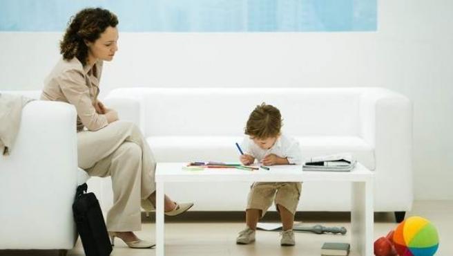 Una mujer, observando a un niño pintar un dibujo.