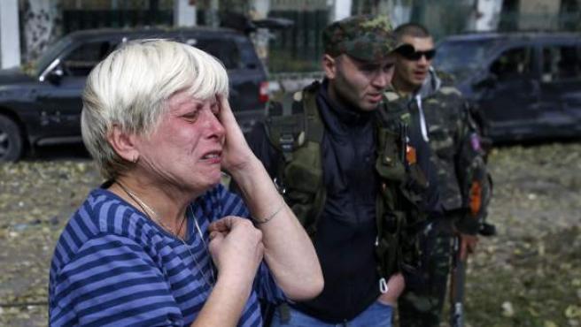 Una mujer llora delante de una escuela dañada por los bombardeos en la ciudad de Donetsk, Ucrania oriental.