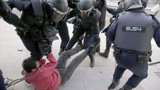 Un grupo de antidisturbios arrastran a un manifestante durante la protesta frente al Parlamento de Galicia en Santiago de Compostela en la que 1.500 personas se oponían al reparto de cuotas de jurel y caballa.