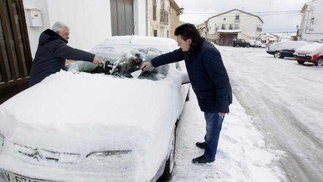 Dos personas retiran el hielo del parabrisas de su vehículo hoy en la Puebla de Valverde, en Teruel, que este miércoles amanecía cubierta de nieve debido al temporal de frío que afecta a gran parte de la península.