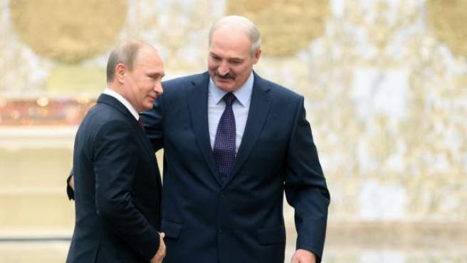 El presidente bielorruso, Alexánder Lukashenko (d), recibe al presidente de Rusia, Vladímir Putin (i), a su llegada a la cumbre de mandatarios cuatripartita para la paz en Ucrania.