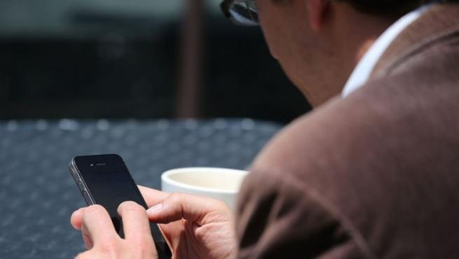 Un hombre escribiendo por el móvil.