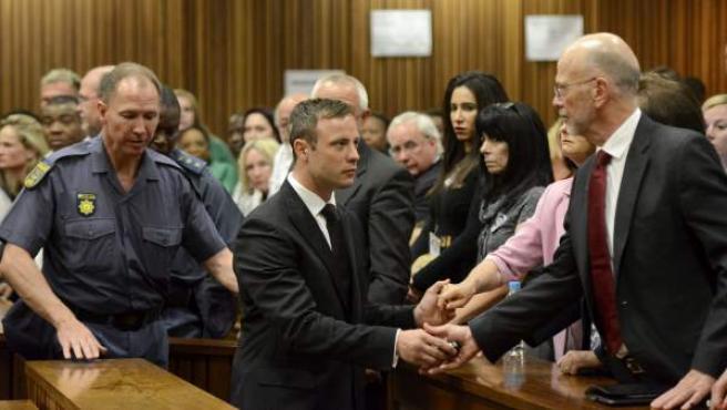 El atleta paralímpico sudafricano Oscar Pistorius (c) se despide de su tio y otros familiares antes de ser trasladado a los calabozos tras ser condenado a cinco años por matar a su novia Reeva Steenkamp, en el Tribunal Superior de Pretoria (Sudáfrica).