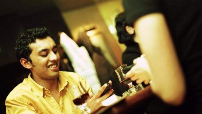 Dos jóvenes usan su teléfono móvil mientras comparten mesa.