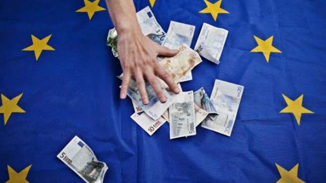 Billetes de euro sobre una bandera de la Unión Europea.