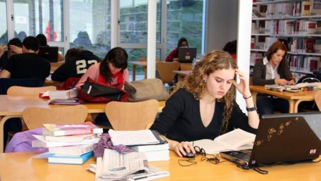 Varios estudiantes repasan libros y apuntes en la biblioteca de una universidad.
