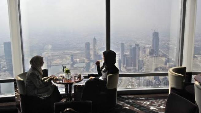 Dos mujeres, comiendo en un restaurante de un rascacielos de Burj Khalifa, en Dubai.