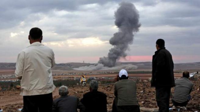 Varias personas observan el humo causado por una explosión contra integrantes de Estado Islámico en la ciudad siria de Kobani.