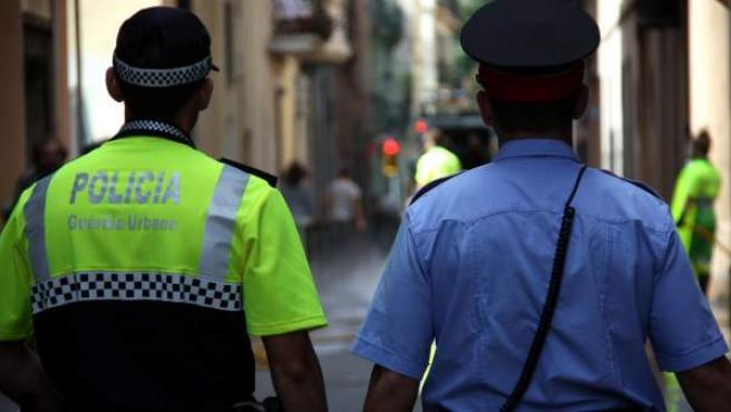 Un mosso d'Esquadra y un agente de la Guardia Urbana patrullan juntos por Barcelona.