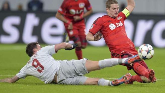 El capitán del Bayer Leverkusen Lars Bender (dcha) pelea por el control del balón con el delantero croata del Atlético de Madrid, Mario Mandzukic (izda), durante el partido de ida de los octavos de final de la Liga de Campeones disputado en Leverkusen, Alemania.