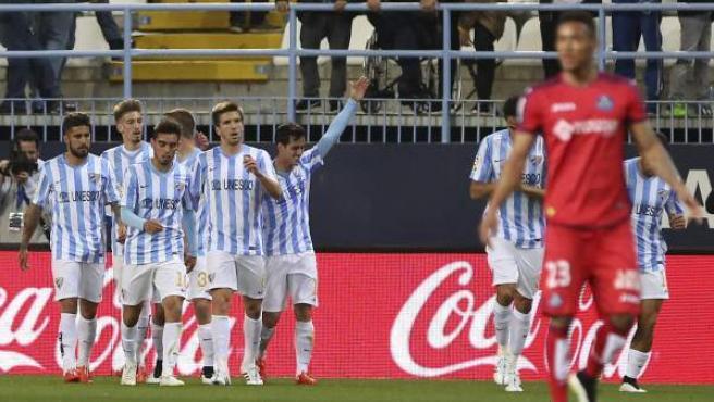 Los jugadores del Málaga CF celebran el primer gol del equipo malacitano, durante el encuentro correspondiente a la vigésimoquinta jornada de Primera División, que disputan frente al Getafe en el estadio de La Rosaleda, en Málaga.