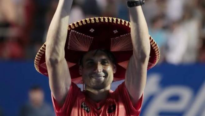 El español David Ferrer posa con el trofeo tras superar al japonés Kei Nishikori y apuntarse su cuarto título en el Abierto Mexicano de tenis.