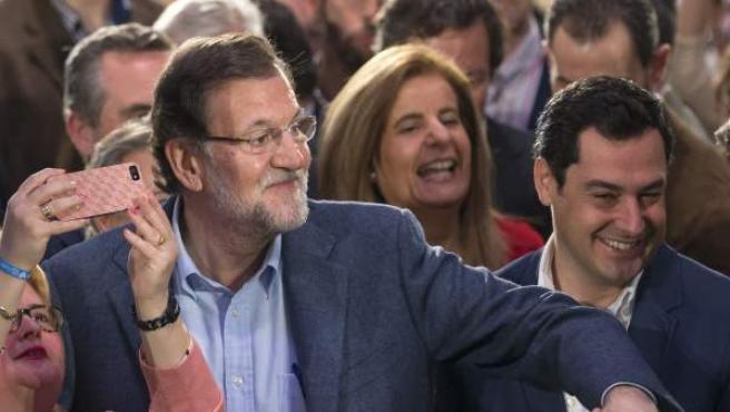 El presidente del Gobierno y del Partido Popular, Mariano Rajoy, la ministra de Empleo, Fátima Báñez y el candidato de esta formación a presidir la Junta de Andalucía, Juanma Moreno (i a d), saludan a los asistentes al comienzo del acto de presentación en Sevilla de los 109 candidatos del PP al Parlamento de Andalucía.