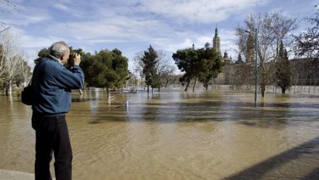 Un hombre fotografía el cauce del río Ebro a su paso por Zaragoza.