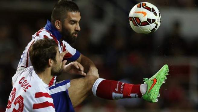 El centrocampista turco del Atlético de Madrid Arda Turan (d) lucha un balón con el defensa del Sevilla Jorge Andújar 'Coke'.