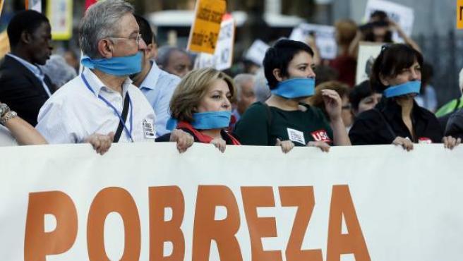 """Varias personas sostienen una pancarta durante la manifestación convocada por Alianza contra la Pobreza bajo el lema """"Contra la riqueza que empobrece, actúa""""."""