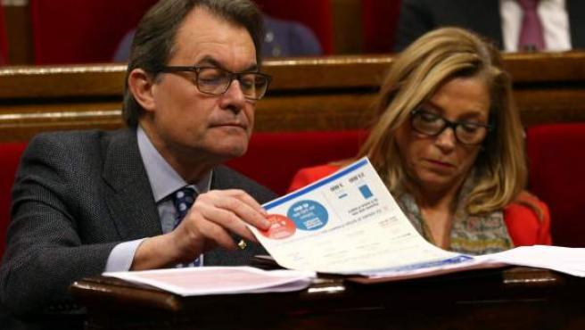 El presidente de la Generalitat (i) repasa unos papeles junto a la vicepresidenta, Joana Ortega (d), en el Parlament.