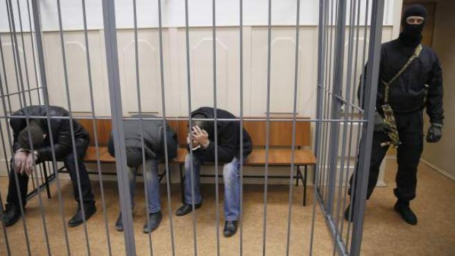 Tres sospechosos no identificados del asesinato del político opositor Boris Nemtsov se ocultan el rostro mientras están sentados en una sala del Tribunal de la ciudad Basmanny en Moscú, Rusia.