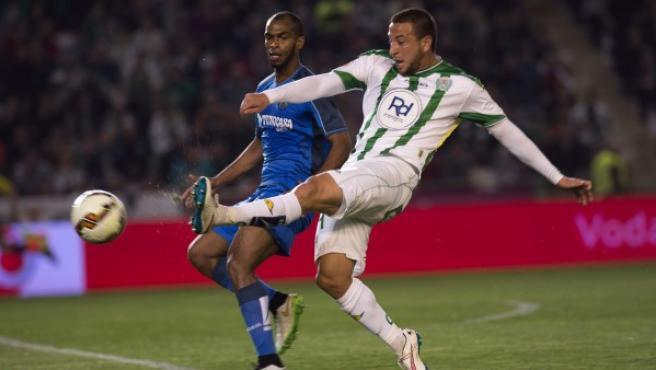 El delantero argelino del Córdoba Nabil Ghilas (d) disputa un balón con el defensa brasileño del Getafe Naldo Gomes (i), durante el partido de la vigésima sexta jornada de la Liga de Primera División.