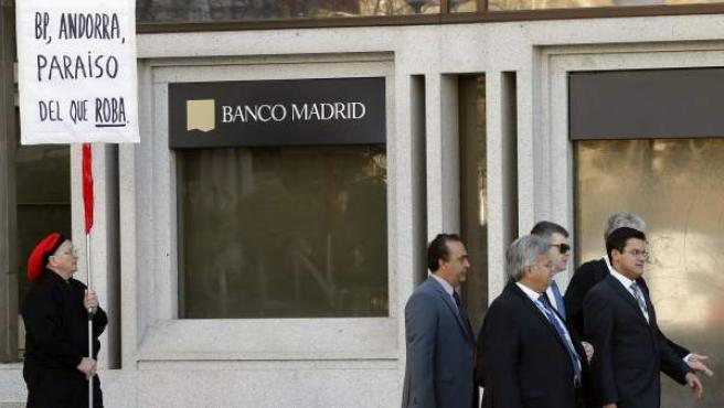 Un hombre protesta ante la sede del Banco de Madrid, intervenido este martes por el Banco de España.