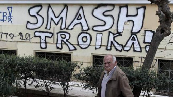 Un hombre camina junto a una pintada en el centro de Atenas (Aplastad a la Troika).