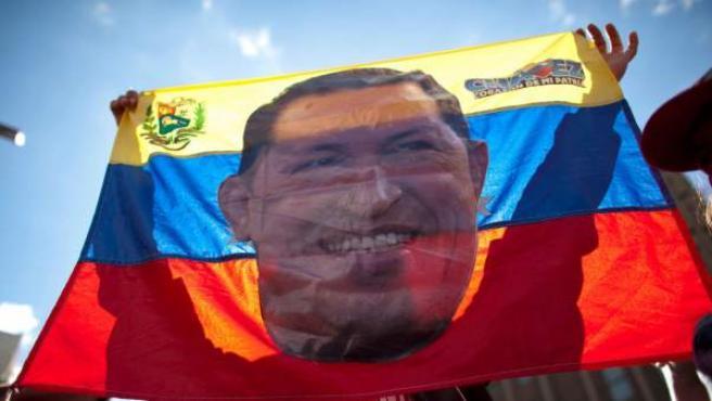 Un seguidor de Chávez sostiene una bandera venezonala con su cara en una manifestación en Caracas.