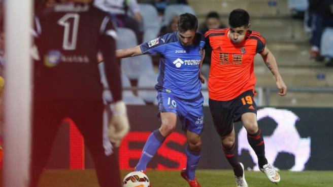 El centrocampista del Getafe Pablo Sarabia (i) lucha un balón con el defensa de la Real Sociedad Yuri Berchiche (d) durante el partido correspondiente a la vigésimo séptima jornada de Liga que disputan en el estadio Coliseum Alfonso de Getafe.