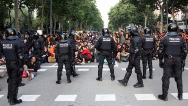 Manifestantes sentados frente al despliegue policial del 15 de junio ante las puertas del Parlament de Cataluña, en el Parc de la Ciutadella.