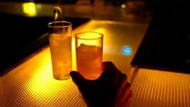 Una persona tomando un combinado de alcohol en un bar de copas.
